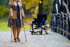 Übendes Gehen der älteren Frau auf Krücken Stockfotos
