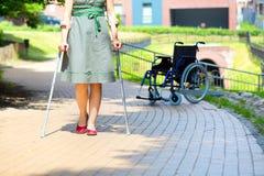 Übendes Gehen der Frau auf Krücken Stockfotos