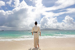 Übendes Karate des jungen Mannes am Strand Stockfotografie