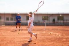 Übendes Tennis des blonden Jungen Stockfotografie
