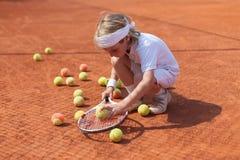Übendes Tennis des blonden Jungen Lizenzfreie Stockfotos