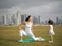 Übendes Yoga der asiatischen chinesischen Frau draußen mit jungem Baby gir stockbild