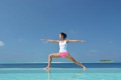 Übendes Yoga der asiatischen chinesischen Frau durch das Meer Stockbild