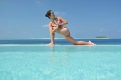 Übendes Yoga der asiatischen chinesischen Frau durch das Meer Stockfotografie