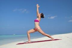 Übendes Yoga der asiatischen chinesischen Frau durch das Meer Lizenzfreies Stockbild