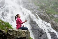 Übendes Yoga der attraktiven Frau auf Felsen nahe schönem Balea-Wasserfall in Rumänien Lizenzfreies Stockbild