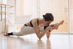 Übendes Yoga der barfüßigfrau im Studio Stockfotos