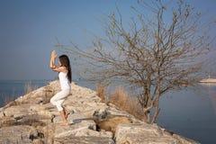 Übendes Yoga der Frau auf dem Strand Lizenzfreie Stockbilder