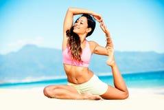 Übendes Yoga der Frau auf dem Strand Stockbilder