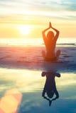 übendes Yoga der Frau auf dem Strand bei erstaunlichem Sonnenuntergang stockfotografie