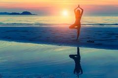 Übendes Yoga der Frau auf dem Strand bei Sonnenuntergang nave lizenzfreie stockfotos