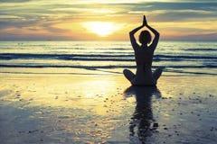 Übendes Yoga der Frau auf dem Strand bei Sonnenuntergang in Thailand lotos stockfoto