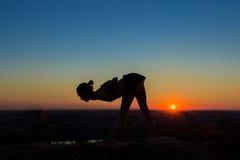 Übendes Yoga der Frau im Park bei Sonnenuntergang Stockfotografie