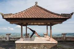 Übendes Yoga der Frau im traditionellen balinesse Gazebo lizenzfreies stockbild