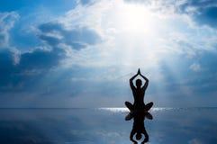 Übendes Yoga der Frau, Schattenbild auf dem Strand bei Sonnenuntergang Lizenzfreies Stockbild