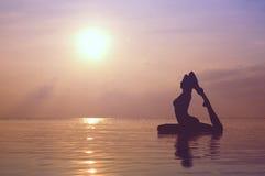 Übendes Yoga der Frau, Schattenbild auf dem Strand bei Sonnenuntergang Lizenzfreie Stockbilder