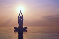 Übendes Yoga der Frau, Schattenbild auf dem Strand bei Sonnenuntergang Stockfotos