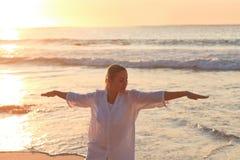 Übendes Yoga der Frau während des Sonnenuntergangs stockfotos