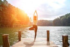 Übendes Yoga der gesunden Frau auf der Brücke Stockfotografie