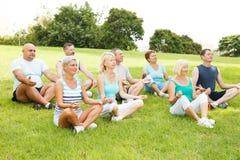 Übendes Yoga der Gruppe von Personen Stockfotos