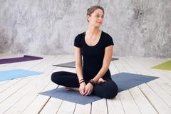 Übendes Yoga der jungen attraktiven Frau, sitzend in Übung Ardha Padmasana, halbe Lotus-Haltung und arbeiten, tragendes Schwarzes Stockfotografie