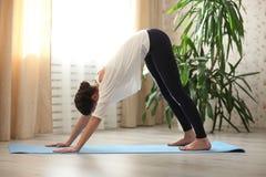 Übendes Yoga der jungen attraktiven Frau, stehend in adho mukha svanasana Übung, abwärtsgerichtete Hundehaltung, Ausarbeiten und  Lizenzfreies Stockbild