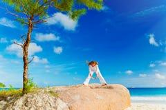 Übendes Yoga der jungen Frau auf dem Felsen Stockbild
