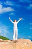 Übendes Yoga der jungen Frau auf dem Felsen Stockbilder