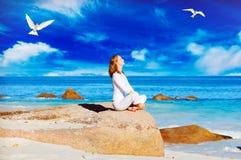 Übendes Yoga der jungen Frau auf dem Felsen Lizenzfreie Stockfotografie