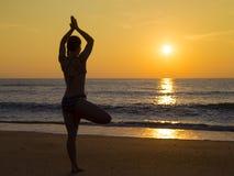 Übendes Yoga der jungen Frau auf dem Strand am Sonnenuntergang Stockfotografie