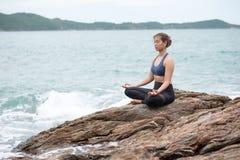 Übendes Yoga der jungen Frau auf einem Felsen in dem Meer Stockfotos