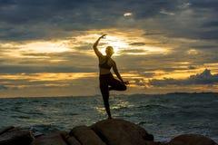 Übendes Yoga der jungen Frau auf einem Felsen in dem Meer Stockbilder