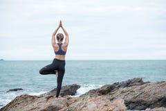 Übendes Yoga der jungen Frau auf einem Felsen am Strand Lizenzfreie Stockfotos