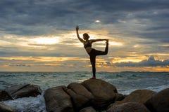 Übendes Yoga der jungen Frau auf einem Felsen am Strand Stockfotografie