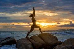 Übendes Yoga der jungen Frau auf einem Felsen am Strand Stockbild
