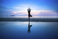Übendes Yoga der jungen Frau auf Strand bei surrealistischem Sonnenuntergang Stockfotos