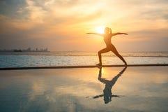 Übendes Yoga der jungen Frau des Schattenbildes Lizenzfreie Stockfotos