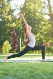 Übendes Yoga der jungen Frau draußen am Park Lizenzfreies Stockfoto