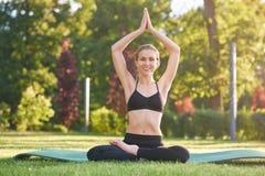 Übendes Yoga der jungen Frau draußen am Park Lizenzfreie Stockfotos
