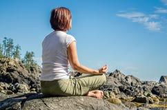 Übendes Yoga der jungen Frau im Freien Stockfoto