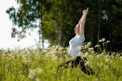 Übendes Yoga der jungen Frau im Freien im Park stockfoto