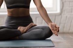 Übendes Yoga der jungen Frau, sitzend in Padmasana-Haltung, Lotus-Übung stockfotografie