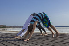 Übendes Yoga der jungen Frau und des Jungen Kinder, stehend in der abwärtsgerichteten Hundeübung Stockbilder