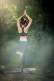 Übendes Yoga der jungen Frau YOGA Rückseite und Entspannung in den Vorderteilen Stockfotos