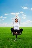 Übendes Yoga der jungen Geschäftsfrau auf der Wiese Stockfotografie