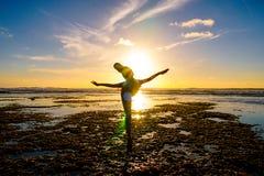 Übendes Yoga der jungen gesunden Frau auf dem Strand bei Sonnenuntergang stockfoto