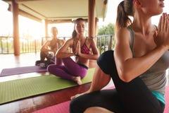Übendes Yoga der jungen Leute in der spinalen Torsionshaltung Stockbild