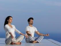 Übendes Yoga der jungen Paare Stockfoto