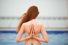 Übendes Yoga der jungen rothaarigen Yogafrau, sitzende Haltung Vajrasana mit einem Namaste hinter der Rückseite, in a arbeiten Stockfotos