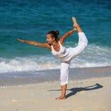 Übendes Yoga der kaukasischen Frau an der Küste Lizenzfreie Stockbilder